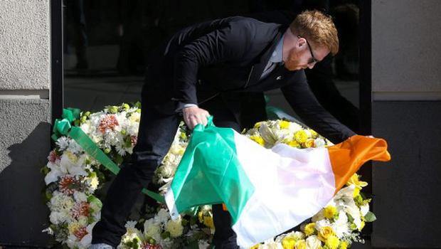 Neil Sands, President of the Irish Network Bay Area, lays an Irish flag atop two wreaths at the scene of a 4th-story apartment building balcony collapse in Berkeley, California June 16, 2015. REUTERS/Elijah Nouvelage