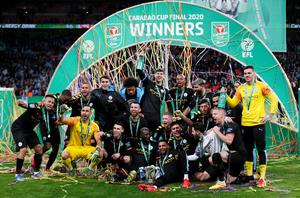 Manchester City players pose with the trophy as they celebrate winning the Carabao Cup