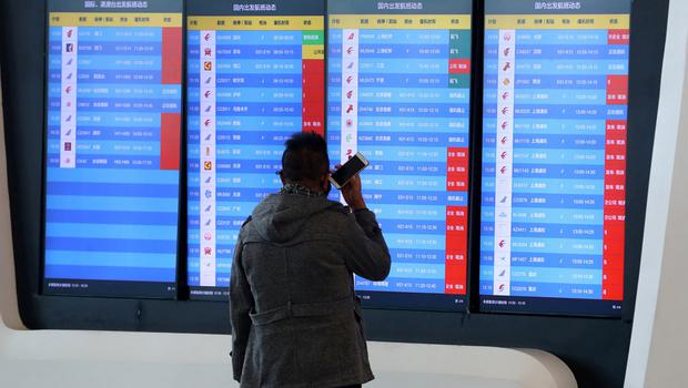 A man stands in front of a screen showing that multiple departure flights have been cancelled after the city was locked down following the outbreak of a new coronavirus, at an airport in Wuhan, Hubei province, China January 23, 2020. cnsphoto via REUTERS