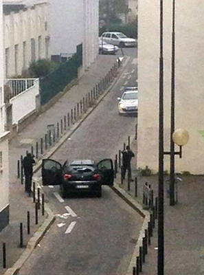 Armed gunmen face police officers near the offices of Charlie Hebdo in Paris