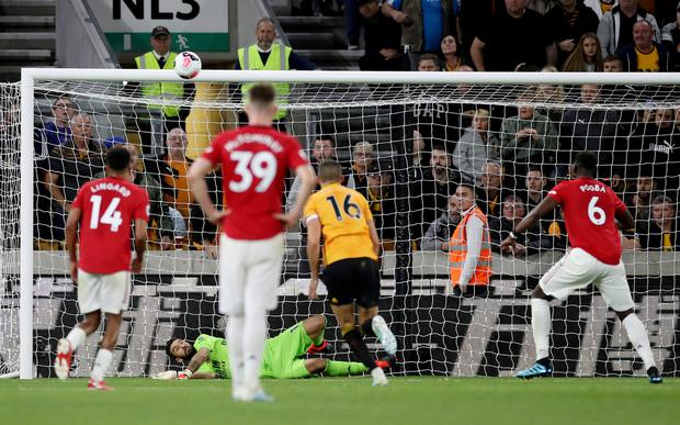 Missed change: Manchester United's Paul Pogba (r) has his penalty saved by Wolverhampton Wanderers' Rui Patricio which would have sent United to the top of the table