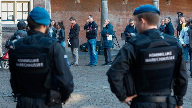 Armed guards watch as voters queue outside a polling station during the Dutch general election in The Hague. Photo: Reuters