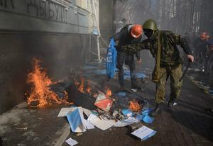 Anti-government protesters burn the Party of the Regions flags, calendars and booklets during a rally in Kiev, February 18, 2014.  REUTERS/Stringer