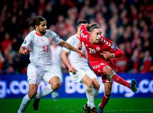 Denmark's Yussuf Poulsen scores the winning goal despite the close attention of Switzerland's Ricardo Rodriguez. Photo by Liselotte Sabroe / Ritzau Scanpix / AFP via Getty Images
