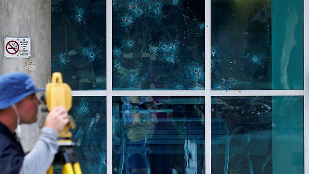 With bullet holes in the side of the Dallas Police headquarters, Bill Smith of the FBI works the scene after an early morning shooting Saturday, June 13, 2015, in Dallas. (AP Photo/Ron Jenkins)