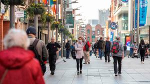 People wear face masks as a precautionary measure against Covid-19, as they walk past shops in Dublin. Photo: PAUL FAITH/AFP via Getty Images