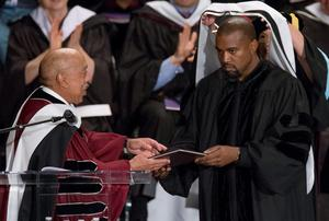 Musician Kanye West (R) receives an honorary doctorate degree from School of the Art Institute of Chicago President Walter Massey during their annual  commencement ceremony in Chicago, Illinois, May 11, 2015. REUTERS/Jim Young