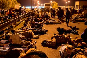 Migrants sleep on a highway in front of a barrier at the border with Hungary