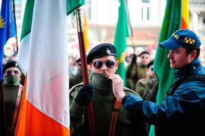 3rd NEWS A Garda Special Detective member removes the face scarf from a member of a republican paramilitary colour party  during the Republican Sinn Fein 1916 centenary commemoration outside the GPO Dublin. Aidan Crawley/ Freelance The Irish Times