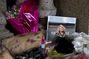 Flowers and a photo, which were left in tribute as part of a makeshift memorial, sit on the steps in front of Joan Rivers' former residence in the Manhattan borough of New York September 6, 2014. Joan Rivers will be laid to rest in a private service on Sunday.  REUTERS/Carlo Allegri
