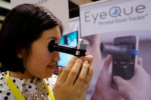 Phoebe Yu of Eyeque Corp., demonstrates her EyeQue Personal Vision Tracker vision testing device attached to a smart phone at CES in Las Vegas, January 3, 2017.  REUTERS/Rick Wilking