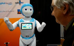 A showgoer looks at the Avatar iPal robot for childen, eldercare and retail  applications at CES in Las Vegas, January 3, 2017.  REUTERS/Rick Wilking