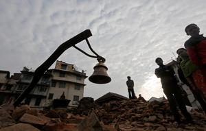 A prayer bell is seen on top of the rubble of a damaged temple after an earthquake in Kathmandu, Nepal April 28, 2015. REUTERS/Adnan Abidi