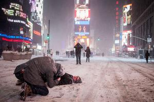 Manhattan resident Jerry Risner lies in the middle of 7th Ave as he has his photographed made by his friend P.J. Chernick during a snow storm in Times Square, New York early morning January 27, 2015.REUTERS/Adrees Latif