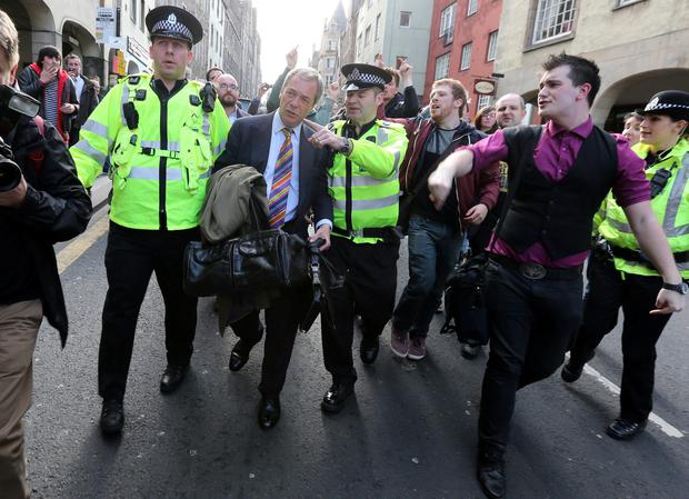 File photo dated 06/05/13 of UKIP leader Nigel Farage being escorted by police officers as he leaves the Cannons Gait pub as protestors heckle him, as the Ukip leader has likened parts of the Scottish nationalism campaign to fascism after being rescued by police when he was mobbed by rowdy protesters. Andrew Milligan/PA Wire