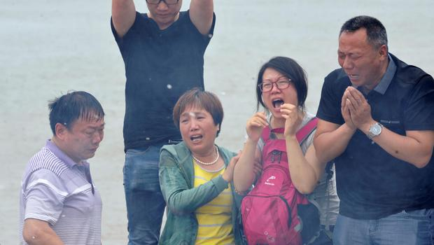 In this photo released by China's Xinhua News Agency, relatives of the victims of the capsized Eastern Star cruise ship mourn at the bank of the Jianli section of the Yangtze River, central China's Hubei Province Sunday, June 7, 2015. (Yu Guoqing/Xinhua via AP)