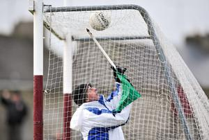 An umpire tries to retrieve a ball caught on the top of the net.