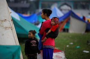 An earthquake victim carries her baby on her back as she stands outside her makeshift shelter on open ground in the early hours in Kathmandu, Nepal April 28, 2015. REUTERS/Adnan Abidi