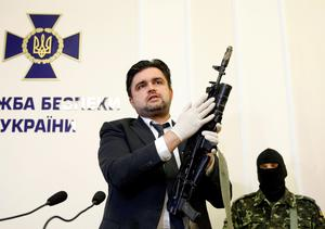 "Markian Lubkivskyi, advisor of the Ukraine's Security Service (SBU) head, demonstrates Kalashnikov automatic rifle with grenade launcher seized from a man, whom according to SBU ia one of two Russian servicemen recently detained by Ukrainian forces, during a news conference in Kiev, Ukraine, May 21, 2015. Ukraine on Monday accused two Russian servicemen it said it had captured of being part of a special forces group that had killed and wounded Ukrainian servicemen in fighting in its eastern regions and said they would be prosecuted for ""terrorist acts"". Russia on Monday restated its position that there were no Russian troops in Ukraine.  REUTERS/Valentyn Ogirenko"