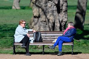 People sit at either end of a park bench as they talk in Clapham Common in south London (Photo by JUSTIN TALLIS/AFP via Getty Images)