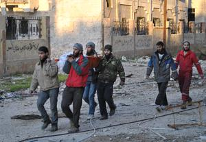 Men carry a body out of the besieged district of the central Syrian city of Homs ahead of being evacuated by United Nations (UN) staff to a safer location, on February 9, 2014.