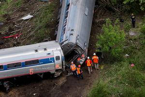 Emergency workers and Amtrak personnel inspect a derailed Amtrak train in Philadelphia, Pennsylvania May 13, 2015.  The commuter rail route where an Amtrak train left the track on Tuesday was not governed by an advanced safety technology meant to prevent high-speed derailments, officials familiar with the investigation said on Wednesday. REUTERS/Lucas Jackson