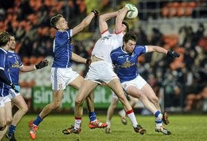 Tyrone's Padraig McNulty claims the ball in the air, under pressure from Cavan's Killian Clarke and Damien O'Reilly