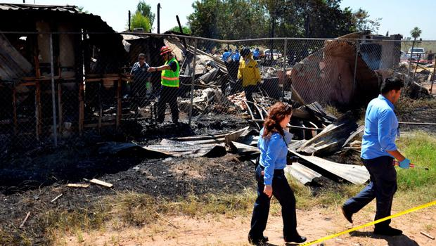 Forensic technicians and firefighters inspect the site of a fire at a nursing home in Mexicali, Mexico, June 23, 2015. REUTERS/Stringer