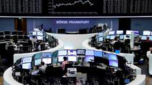 Traders work at their screens in front of the German share price index DAX board at the stock exchange in Frankfurt. Photo: Reuters