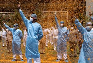 Tribute: Hospital staff are showered with flower petals by a navy helicopter as part of an event to thank frontline staff in Mumbai, India. AP Photo/Rajanish Kakade