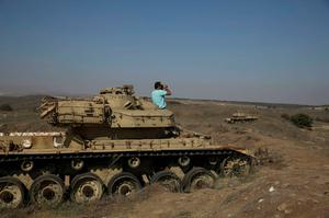 A man stands on an old tank in the Israeli occupied Golan Heights as he uses binoculars to watch fighting in Syria. Israel shot down a Syrian warplane on Tuesday, saying the aircraft crossed the battle lines of Syria's civil war and flew over the Israeli-held Golan Heights, perhaps by accident. Reuters
