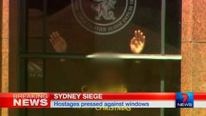 Hands are pressed up against the window of the Lindt cafe, where hostages are being held. Photo: Reuters TV via Seven Network