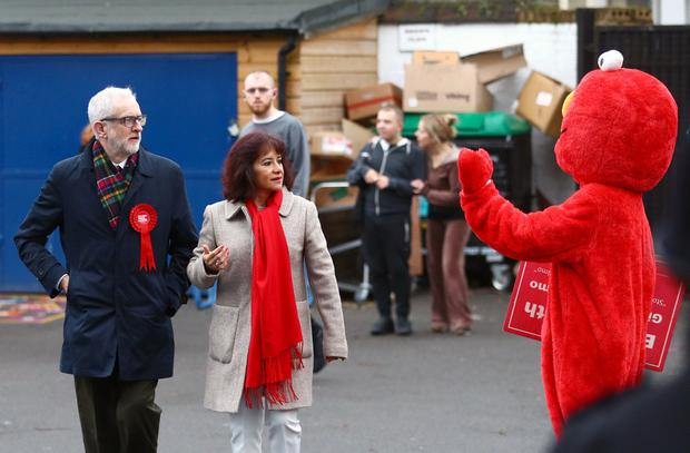 Britain's opposition Labour Party leader Jeremy Corbyn and his wife Laura Alvarez look on as a person in a costume of Sesame Street character Elmo waves, as they arrive at a polling station to vote in the general election in London, Britain, December 12, 2019. REUTERS/Hannah McKay