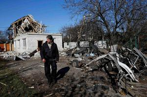 """A man walks past a residential block and a car damaged by recent shelling in Donetsk, eastern Ukraine, November 6, 2014. Kiev said on Wednesday it would halt payment of state funds in areas controlled by pro-Moscow rebels, as both sides hardened positions in what is rapidly becoming a """"frozen conflict"""": a long-term stalemate that the West believes is Russia's aim (REUTERS/Maxim Zmeyev)"""
