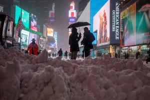 Commuters stand under an umbrella next to snow which was being plowed to the street edge from a walkway in Times Square, New York on January 26, 2015.  REUTERS/Adrees Latif