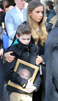 Oisin Drury carrys a picture of his dad, Paul with his pictured with his sister at Mr Drury's funeral