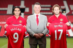 New Manchester United signings Radamel Falcao (L) and Daley Blind (R) pose with manager Louis Van Gaal during a photocall at Old Trafford in Manchester