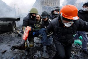 Anti-government protesters carry a man with a bullet wound on his leg during clashes with riot police