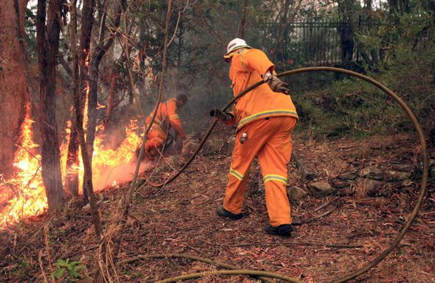 A Rural Fire Service fire-fighter runs to help a colleague who fell near flames while spraying water on a small fire burning near a home in the Blue Mountains suburb of Faulconbridge