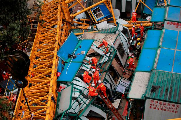 Rescuers work at the accident site of a collapsed temporary structure after it was hit by a crane on a construction site in Mayong Township of Dongguan City, south China's Guangdong Province on April 13, 2016