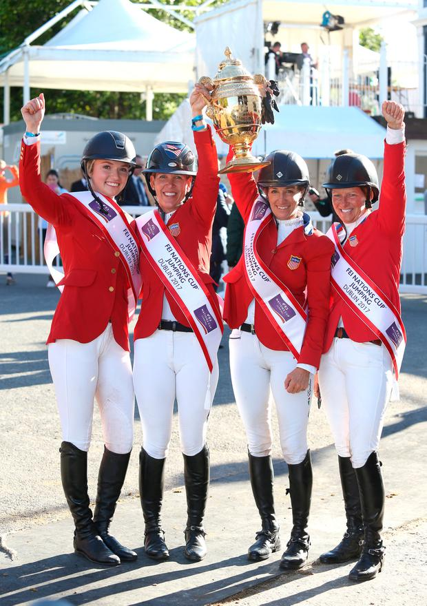 The American team, from left to right, Lillie Keenan, Lauren Hough, Laura Kraut and Elizabeth Madden celebrate with the Aga Khan trophy after winning the Nations Cup