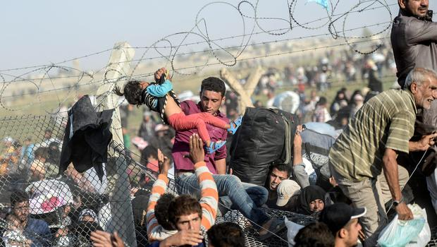 A man carries a girl as Syrians fleeing the war pass through broken-down border fences to enter Turkish territory illegally