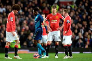 Manchester United players look dejected after Arsenal's Danny Welbeck (second from left) scores his sides second goal of the game during the FA Cup, Sixth Round match at Old Trafford