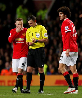 Manchester United's Wayne Rooney talks with referee Michael Oliver after Marouane Fellaini was shown a yellow card Action Images via Reuters / Jason Cairnduff