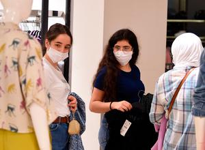 Shoppers, wearing protective face masks, shop at a clothing store in the Tunisian capital Tunis. (Photo by FETHI BELAID / AFP) (Photo by FETHI BELAID/AFP via Getty Images)
