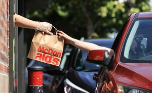 Mcdonalds re-opens.  Customers collect their orders through the window at the McDonalds drive thru on the Malahide road in Dublin .   Picture; Gerry Mooney