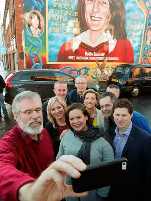 Sinn Fein's Michelle O'Neill (centre left), Mary Lou McDonald (centre right) and Gerry Adams (left) pose for a selfie in front of the Bobby Sands mural after post election press conference at Sinn Fein headquarters in Belfast. Photo: Niall Carson/PA Wire