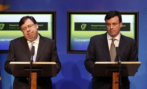 Taoiseach Brian Cowen reacts as the Minister for Finance Lenihan  speaks to the media in Government Buildings Dublin on November 21 2010
