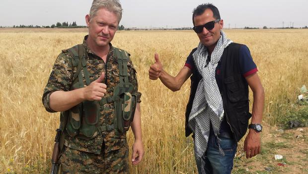 Michael Enright, left, a British actor who has had minor roles in Hollywood films, gives a thumbs up with Kurdish journalist Mohammed Hassan, right, as he holds his AK-47 and wears the Kurdish fighters military uniform after he joined them battling against the Islamic State group, at Tel Khenzeer village, near Ras el-Eyn town, northeast Syria. (Mohammed Hassan via AP )
