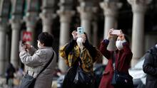 People wearing masks take pictures at Duomo square, as a coronavirus outbreak continues to grow in northern Italy, in Milan, Italy, February 26, 2020. REUTERS/Yara Nardi